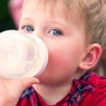 After the first year of age, is cow's milk or formulated milk more suitable?
