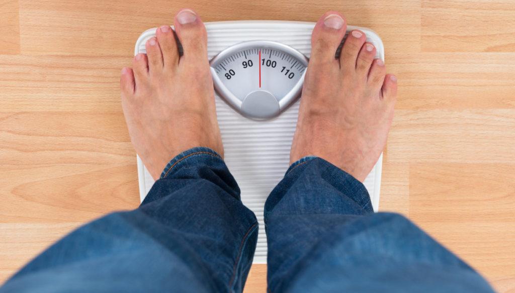 persona che si pesa su bilancia
