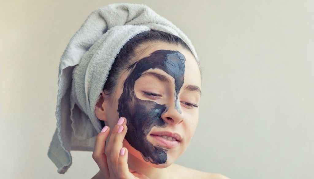Woman applies black mask on her face