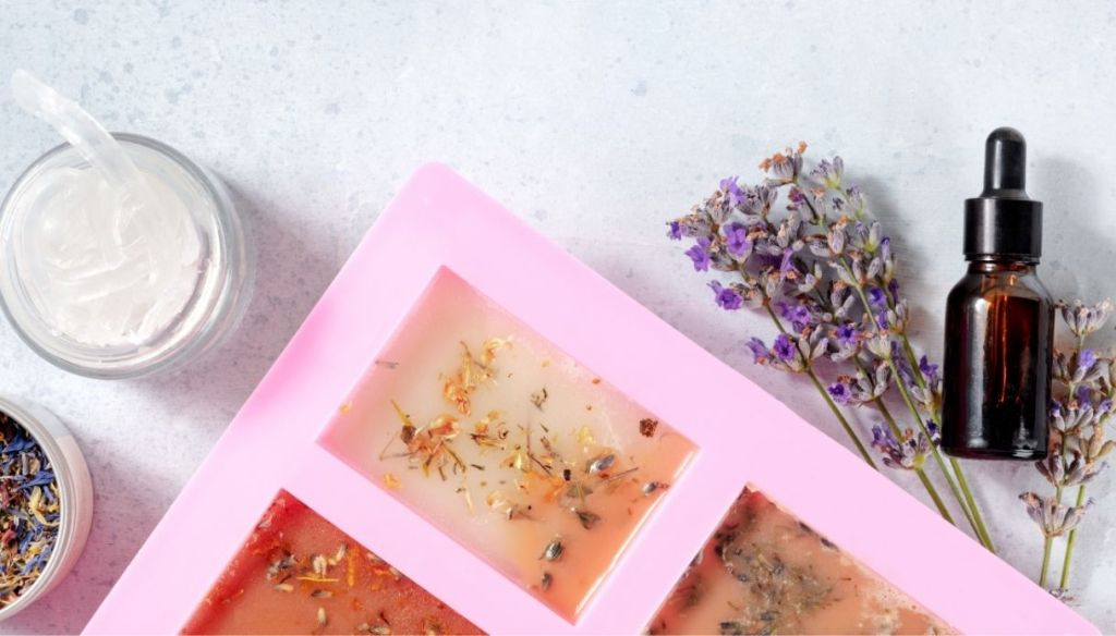 silicone mold with soap, flowers, lavender, dark bottle and petals