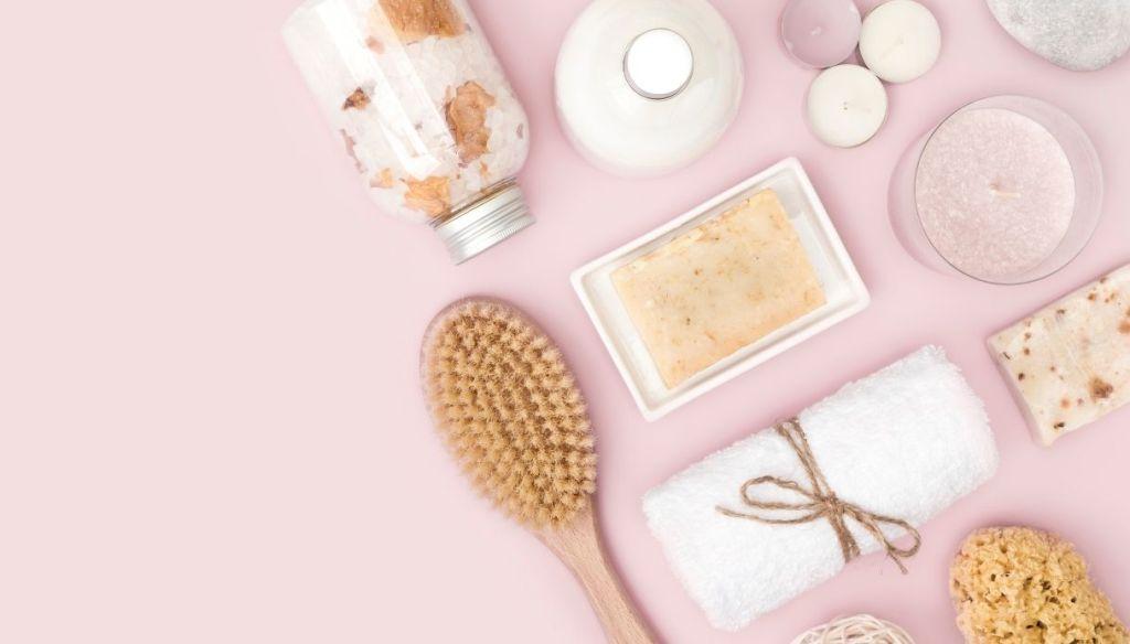 pink surface with brush, towel, sponge, bath salts, soap, candles, bubble bath