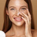 Donna con i capelli rossi applica la crema sul naso