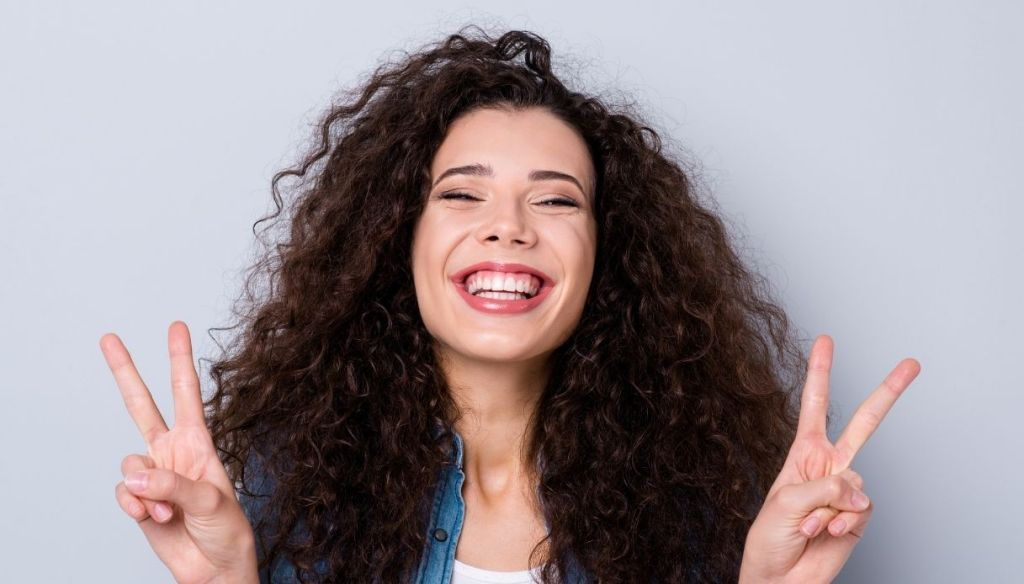 brunette girl with voluminous curly hair smiles and cheers with her fingers
