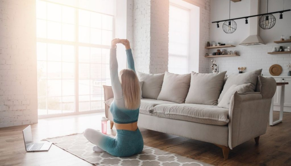 young blonde girl in light blue sports suit stretching in bright living room with gray sofa
