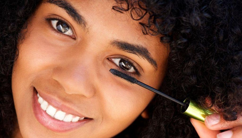 Black mulatto afro curly hair girl smiling applies mascara