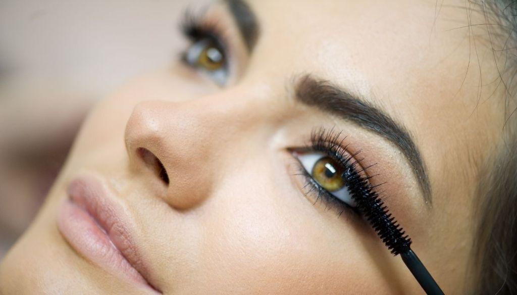 Close up girl green eyes makeup applying mascara