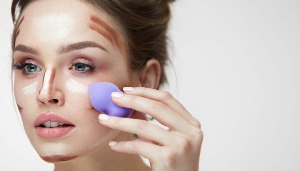 ragazza capelli legati applica makeup con spugnetta trucco beauty blender contouring
