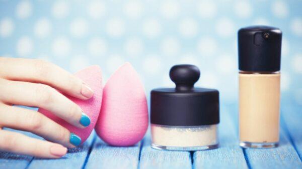 mano con smalto colorato spugnette trucco cipria e fondotinta su sfondo azzurro