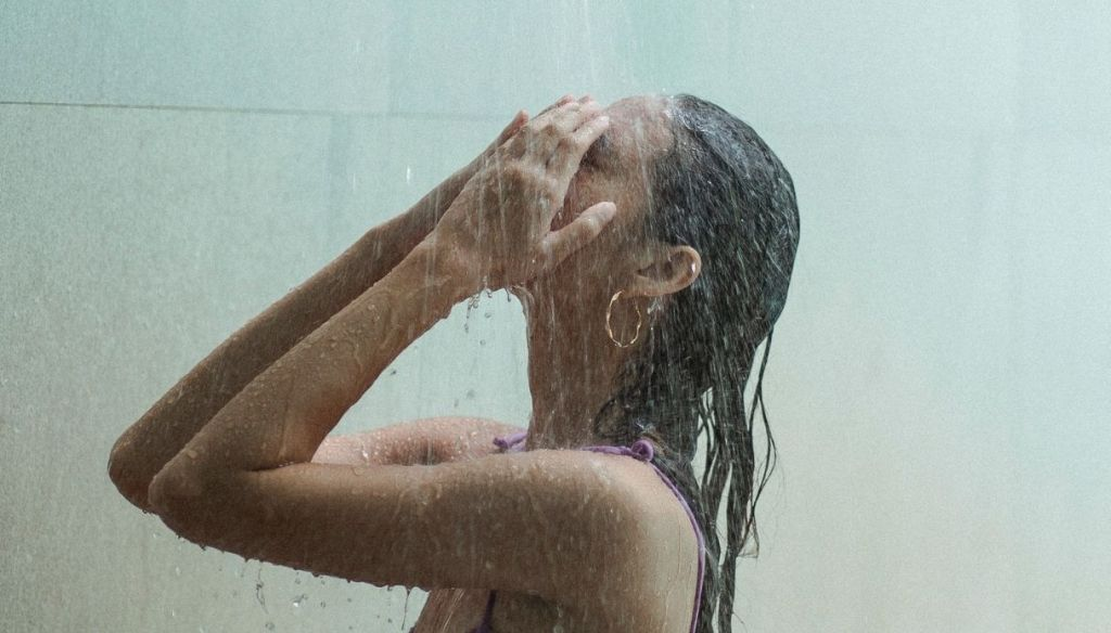 girl in purple bathing suit with closed eyes washes hair rinse under shower