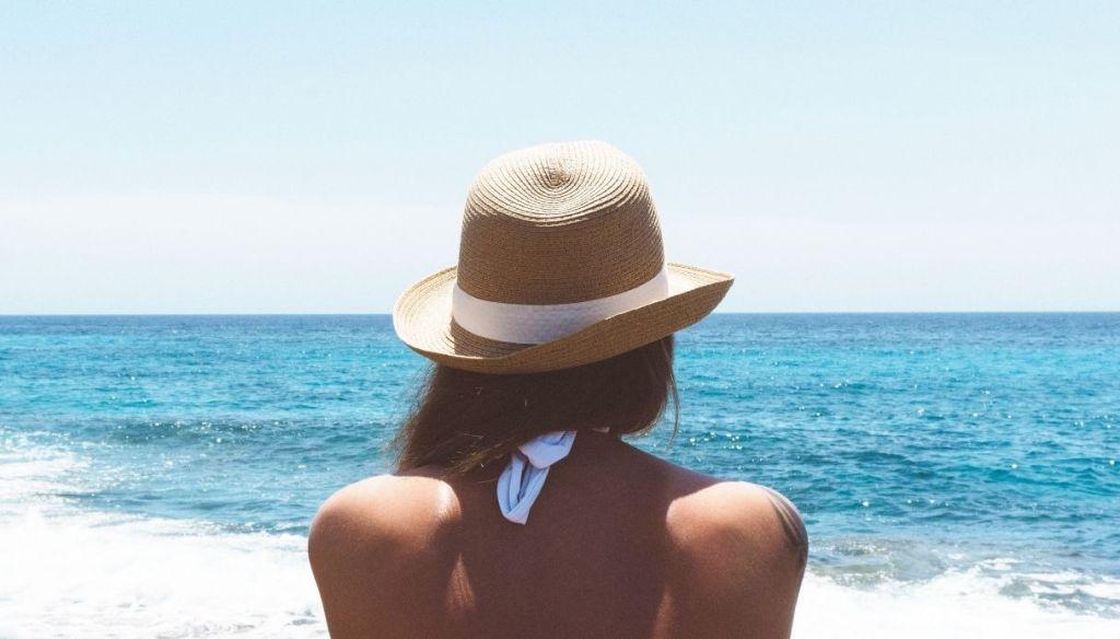 shoulders girl sunbathes with golden tan hat