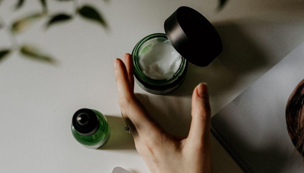 female hand skincare cream jar