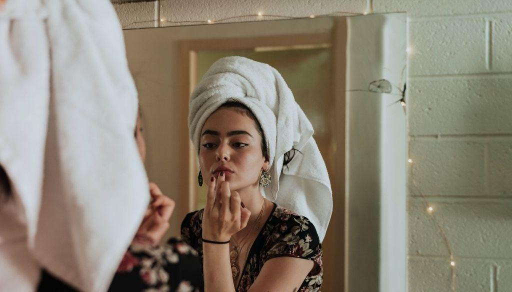 turban brunette girl applies lip balm