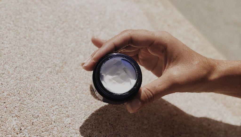 female hand eye face cream jar