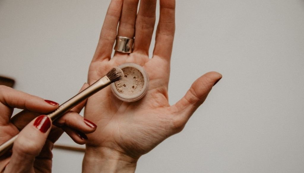 hand with loose powder and brush